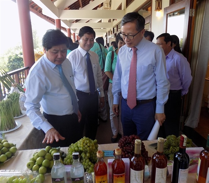 Deputy Minister of Agriculture and Rural Development Lê Quốc Doanh (left) introduces some food to FAO guests, at an event held in southern Ninh Thuận Province on Friday to mark World Food Day in Việt Nam. — Photo nongnghiep.vn