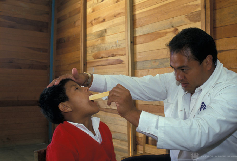 Doctor looks at boy's throat in medical examination. Mexico. Photo: © Curt Carnemark / World Bank