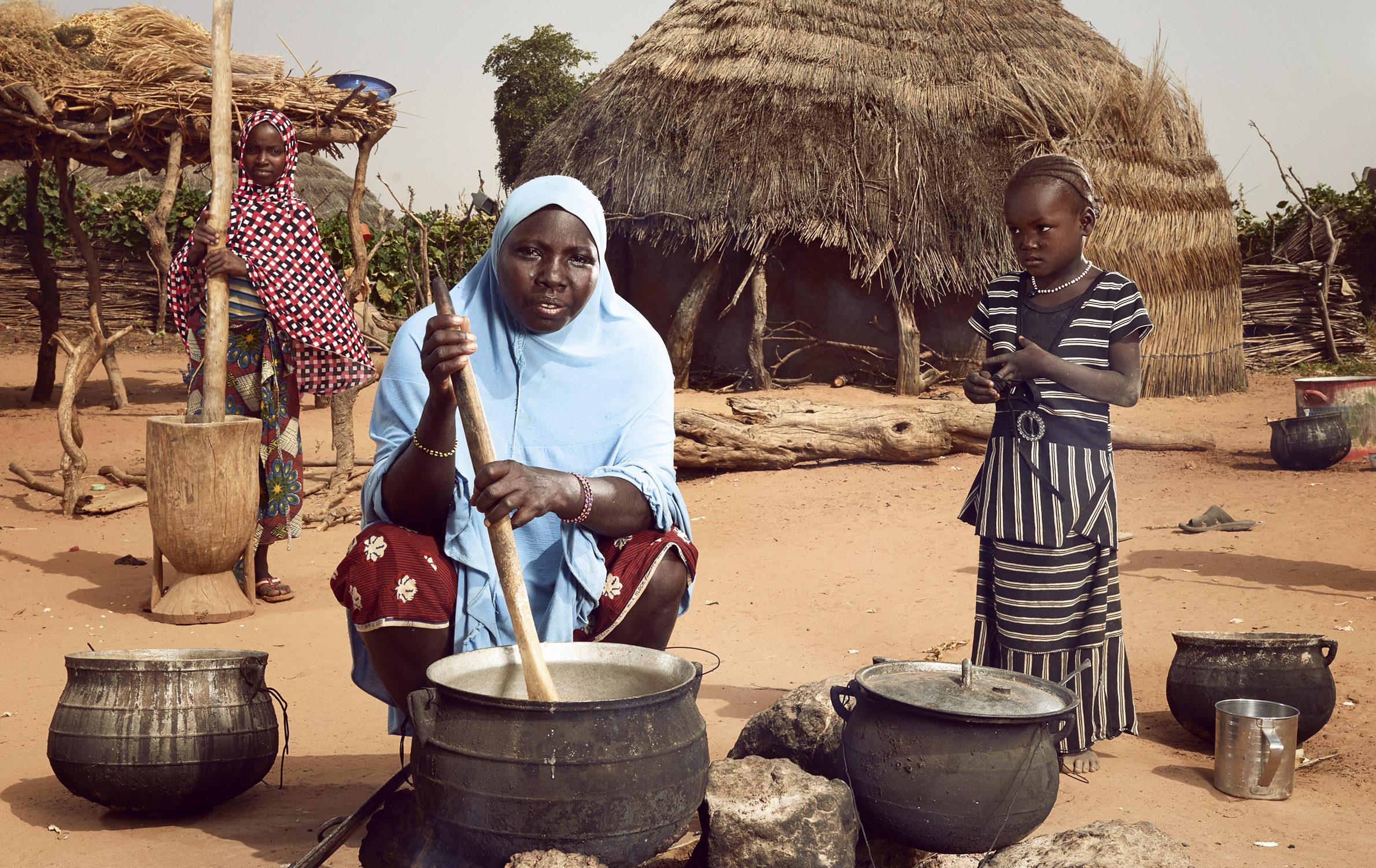 Hadiza (au centre) prépare un repas familial, aidée par ses filles Nadia, 4 ans, et Layhanatou, 10 ans, qui pilent le millet dans un mortier en bois. Photo : © Stephan Gladieu/Banque mondiale